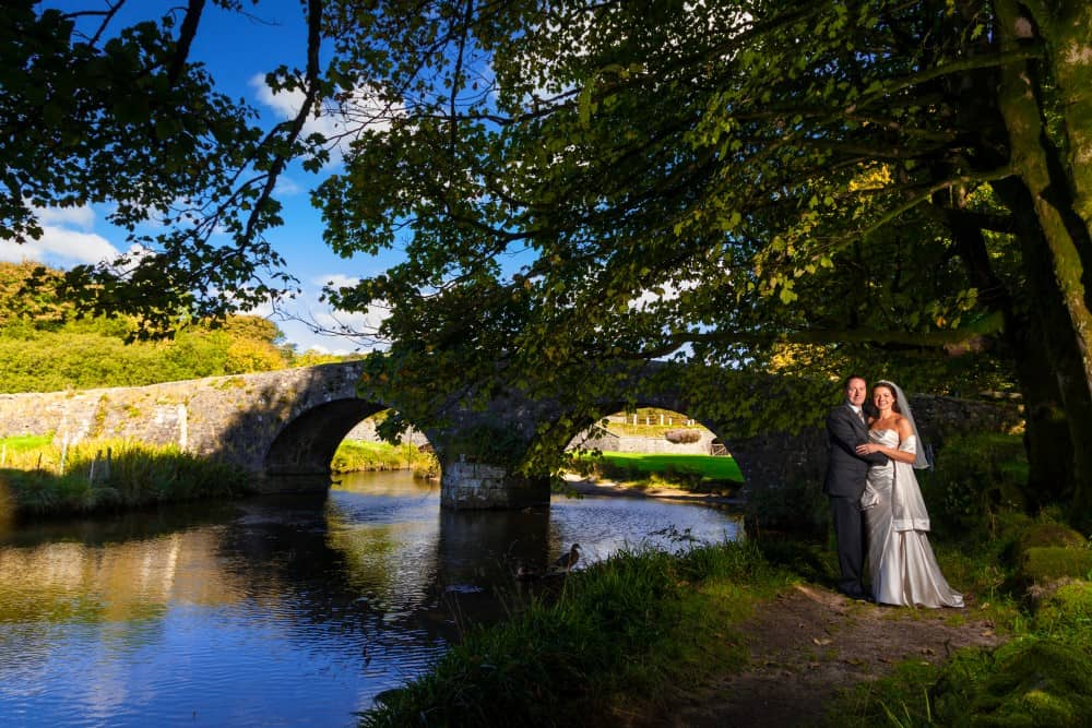 Bride and groom by river at Two Bridges Hotel on wedding day