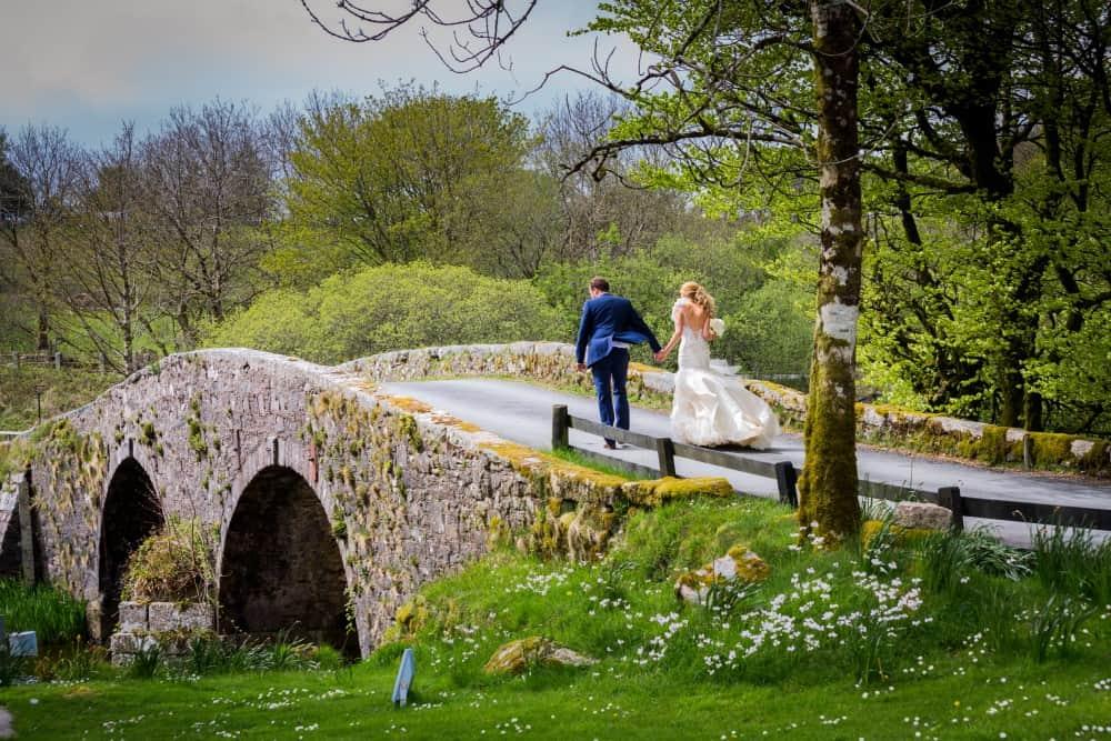 Bride and groom on bridge at Two Bridges Hotel