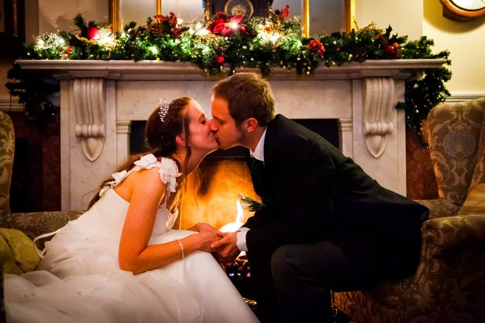 Bride and groom share a kiss by the fire at Two Bridges Hotel